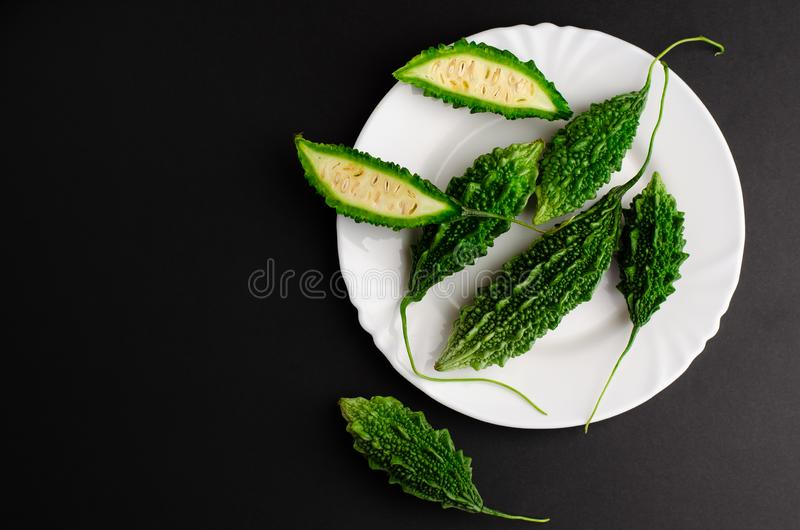 Bitter cucumber on white plate on black background. Cooking concept. Copy space, top view royalty free stock photography