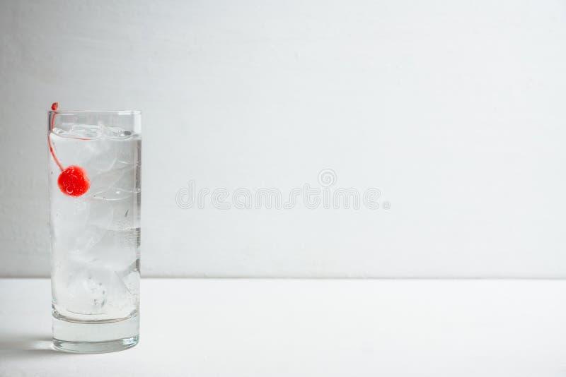 Bitter genomskinlig coctail med coctailkörsbäret fotografering för bildbyråer