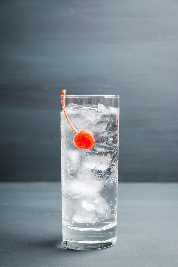 Bitter genomskinlig coctail med coctailkörsbäret royaltyfria foton
