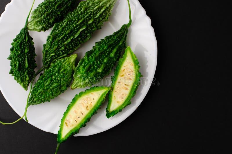 Bitter Gurken auf weißer Platte auf schwarzem Hintergrund Exotische Lebensmittelkonzepte Leerzeichen kopieren, obere Ansicht stockfotos