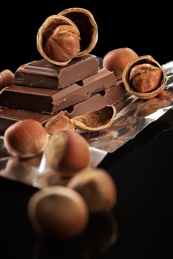 Bittere dunkle Schokolade in einer Folie und in den Muttern lizenzfreie stockbilder