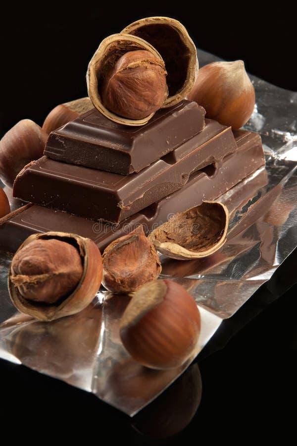 Bittere dunkle Schokolade in einer Folie und in den Muttern lizenzfreie stockfotografie