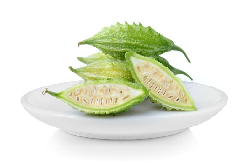 Bittermelon in der weißen Platte auf weißem Hintergrund stockfotos