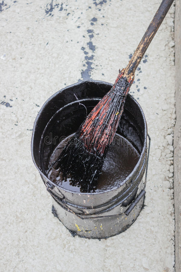 Bitumen Emulsion In Metal Bucket Which Is Applied With A Broom Royalty Free Stock Photo