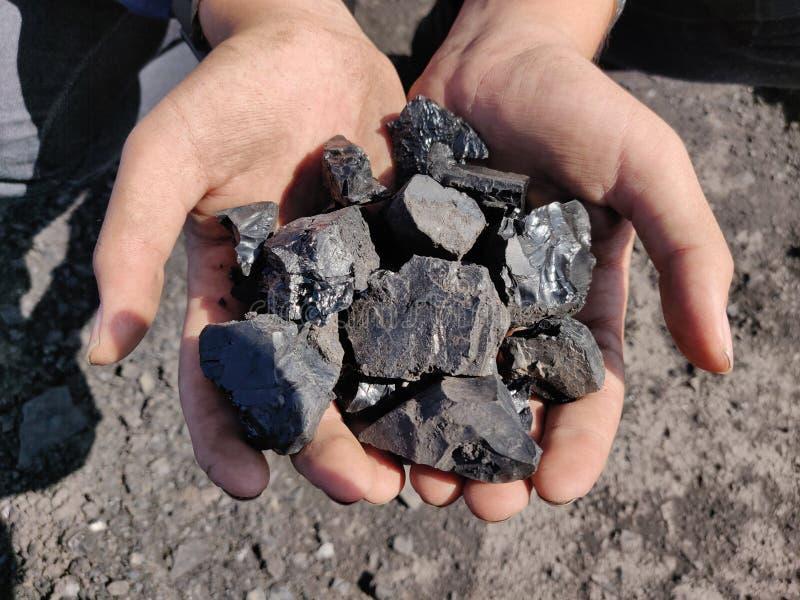 Bitumiczny węgiel na ręce zdjęcia stock