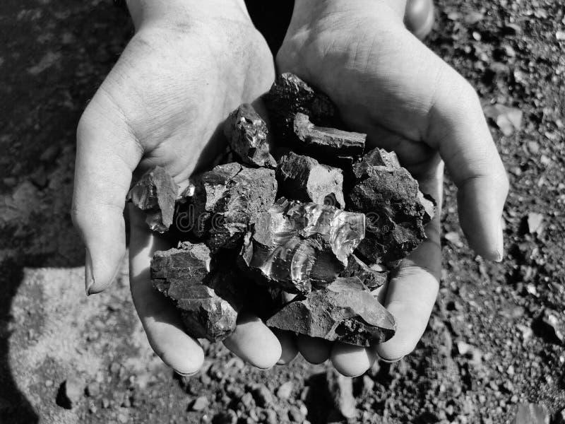 Bitumiczny węgiel na ręce, czarny i biały fotografia obraz royalty free