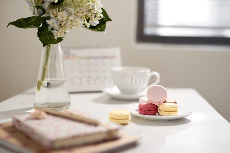 Biura stołowy biurko Kobieca biurka workspace rama z kalendarzem, dzienniczkiem, hortensia bukietem, macaron i kawą na białym tle fotografia royalty free