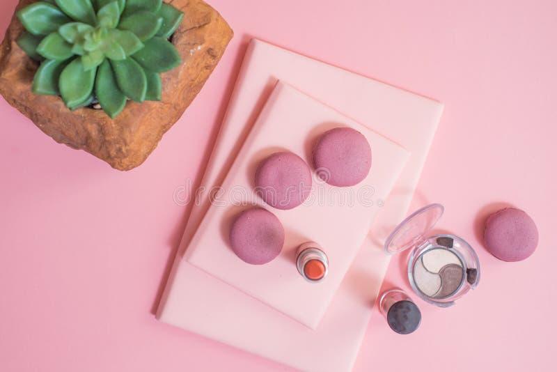 Biurko na różowych szkła notepad kopania ołówkach zasadza macaroons budzika Odgórnego widok obrazy stock