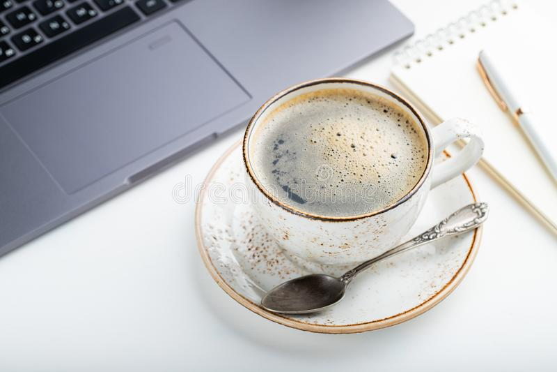 Biurko z laptopem, oczu szkłami, notepad, piórem i filiżanką kawy na białym stole, Lekki tło obrazy stock