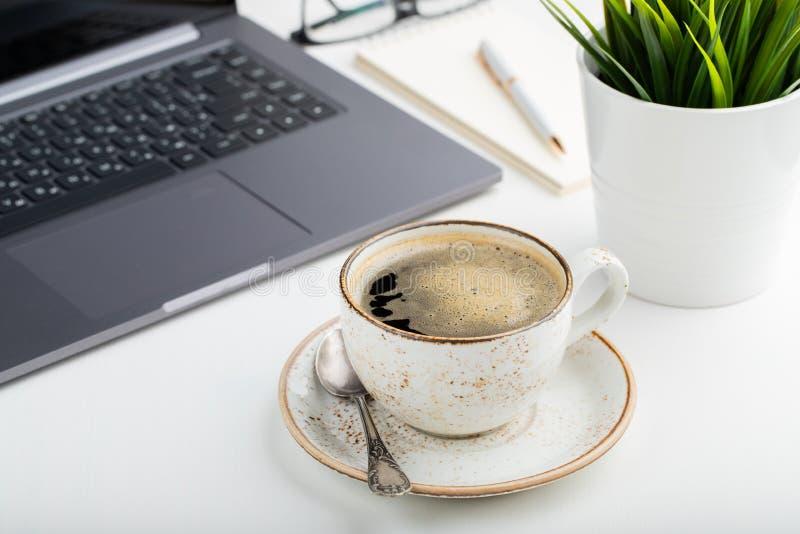 Biurko z laptopem, oczu szkłami, notepad, piórem i filiżanką kawy na białym stole, Lekki tło zdjęcie royalty free