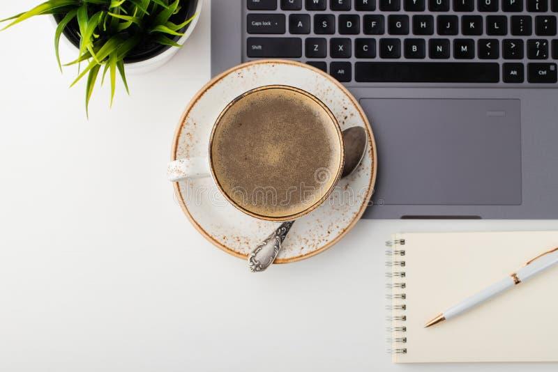 Biurko z laptopem, oczu szkłami, notepad, piórem i filiżanką kawy na białym stole, Odgórny widok z kopii przestrzenią Mieszkanie  fotografia stock