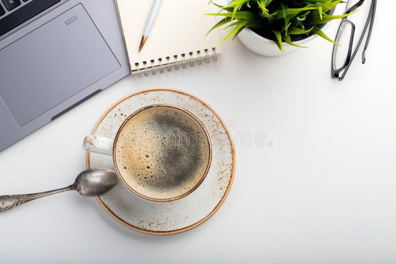 Biurko z laptopem, oczu szkłami, notepad, piórem i filiżanką kawy na białym stole, Odgórny widok z kopii przestrzenią Mieszkanie  obraz royalty free