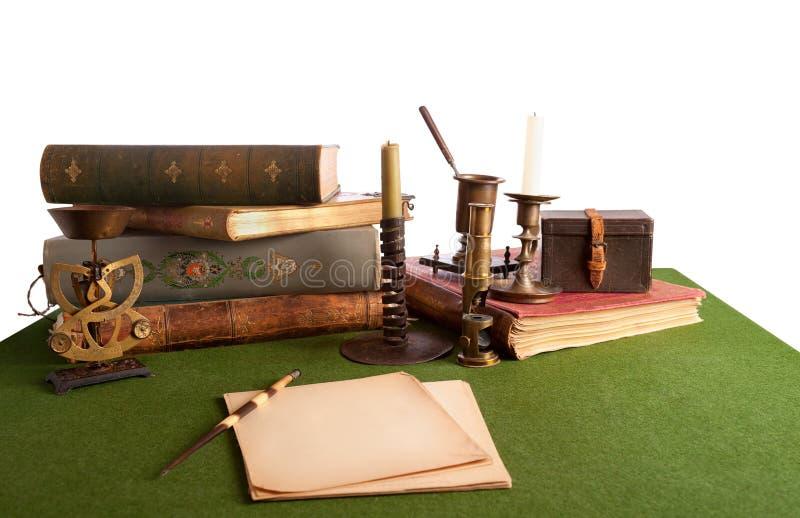 Biurko z otwartą książką i starym materiały. Odizolowywa zdjęcia stock