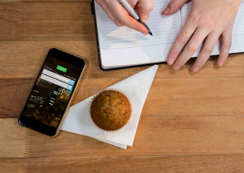 biurko z telefonem, słodka bułeczka i rękami z agendą, royalty ilustracja