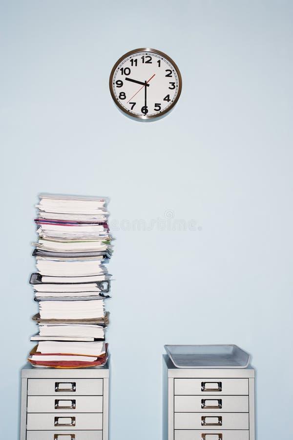 Biuro ściana z zegarową stertą papierkowa robota w inbox na kartoteka gabinecie zdjęcia royalty free