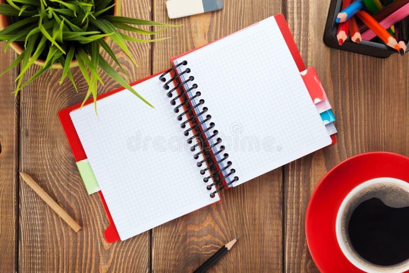 Biuro stół z kwiatem, pustym notepad i filiżanką, obrazy royalty free