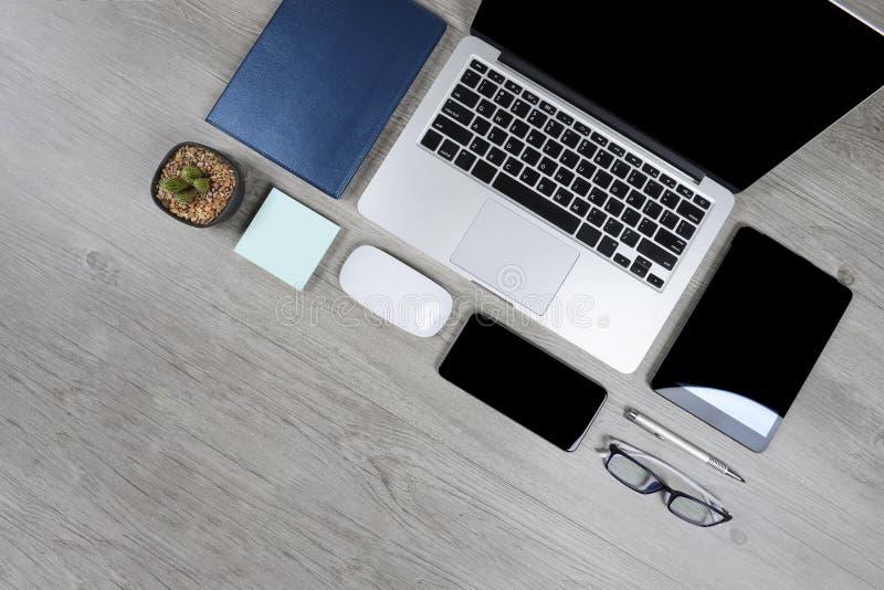 Biuro stół z laptopem, notatnikiem, cyfrową pastylką, piórem, smartphone, myszą, eyeglasses i kawą na drewnianym tle, obraz stock