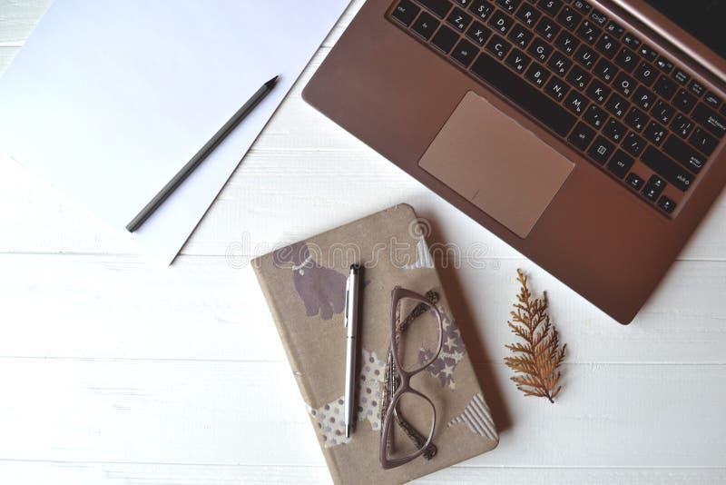 Biuro stół z laptpo, notatnikiem, piórem, ołówkiem, szkłami, portflem i białym papierem, zdjęcia royalty free