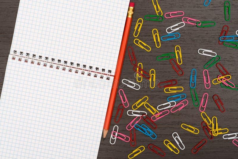 Biuro stół z notatnikiem, ołówkami i papierowymi klamerkami, zdjęcie stock