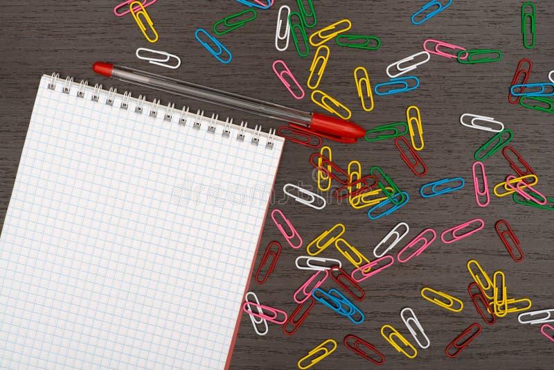 Biuro stół z notatnikiem, piórem i papierowymi klamerkami, zdjęcia stock