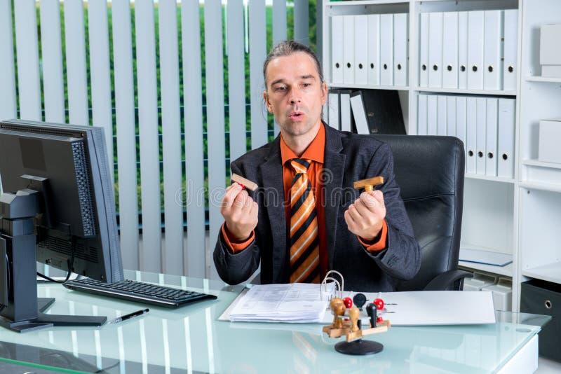 Biurokracja biznesowy mężczyzna patrzeje znaczki przy jego biurkiem obrazy stock