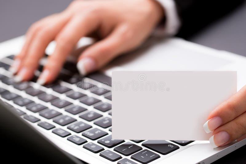 Biurowa kobieta jest pisać na maszynie pustą biel kartę i trzymająca zdjęcie royalty free