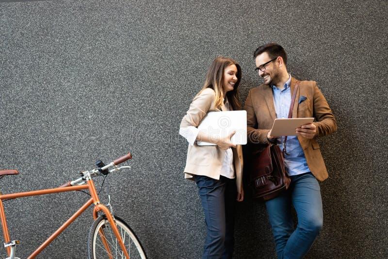 Biurowa kobieta z biznesowego mężczyzny parą cieszy się przerwę podczas gdy opowiadający flirtować plenerowy obraz royalty free