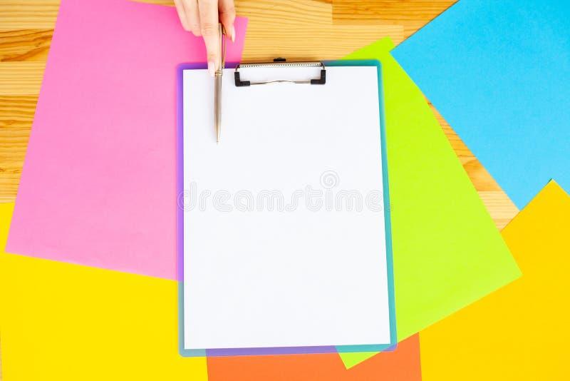 Biurowa ręka Trzyma falcówkę z Białym koloru papierem i pióro na Barwionym tle Drewniany stół Copyspace Miejsce dla zdjęcia stock