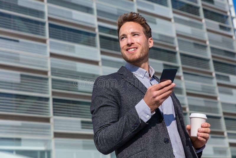 Biurowej pracy mężczyzny biznesmena mienia wiszącej ozdoby przyglądający oddalony telefon komórkowy Młody miastowy fachowy mężczy obraz royalty free