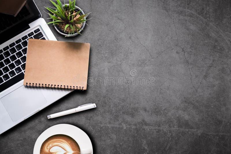 Biurowi akcesoria laptop, smartphone, notepad i filiżanka na, Cementują ściany stołowego tło fotografia royalty free