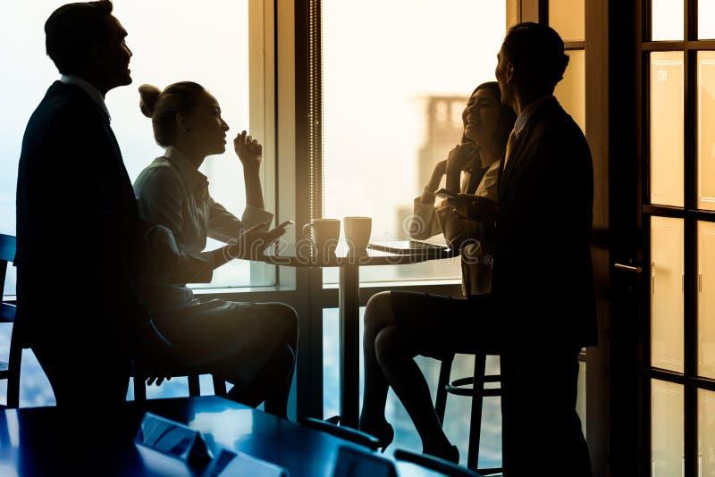 Biurowi pracownicy ma kawową przerwę i opowiadać zdjęcia stock