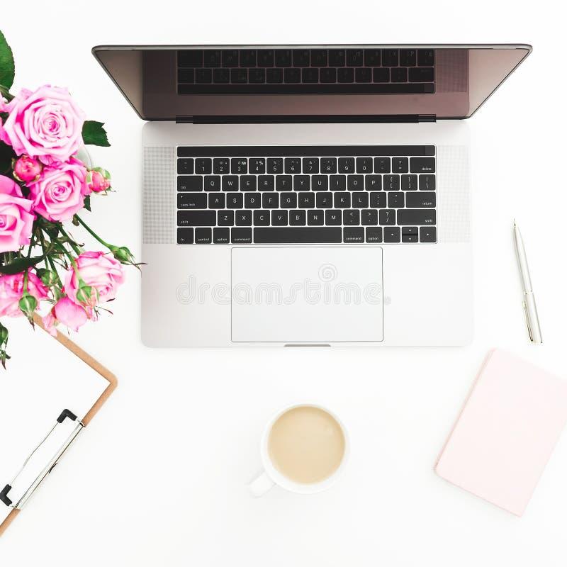 Biurowy biurko z żeńskim workspace z laptopem, różowy róża bukiet, kawowy kubek, różowy dzienniczek na białym tle Mieszkanie niea zdjęcia stock