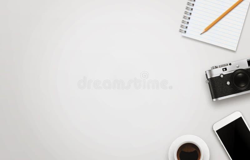 Biurowy biurko z bezpłatną przestrzenią dla teksta Kamera, filiżanka kawy, mądrze telefon, notepad, ołówek na bielu stole zdjęcie stock
