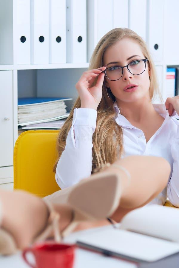 Biurowy flirt - atrakcyjna kobieta flirtuje nad biurkiem z jej szefem lub coworker fotografia stock