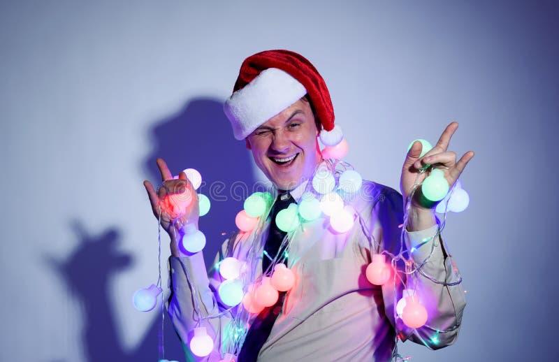 Biurowy mężczyzna w Święty Mikołaj czerwonej nakrętce z barwionymi girlandami fotografia royalty free