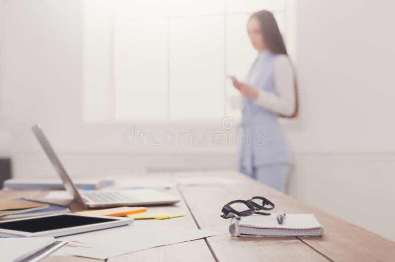 Biurowy miejsce pracy z dostawami, zamazana kobieta zdjęcie royalty free