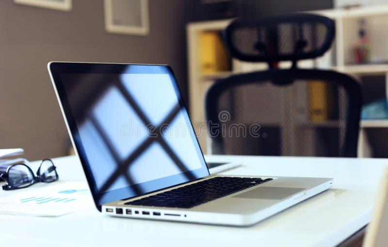 Biurowy miejsce pracy z laptopem na drewno stole przeciw okno zdjęcia royalty free