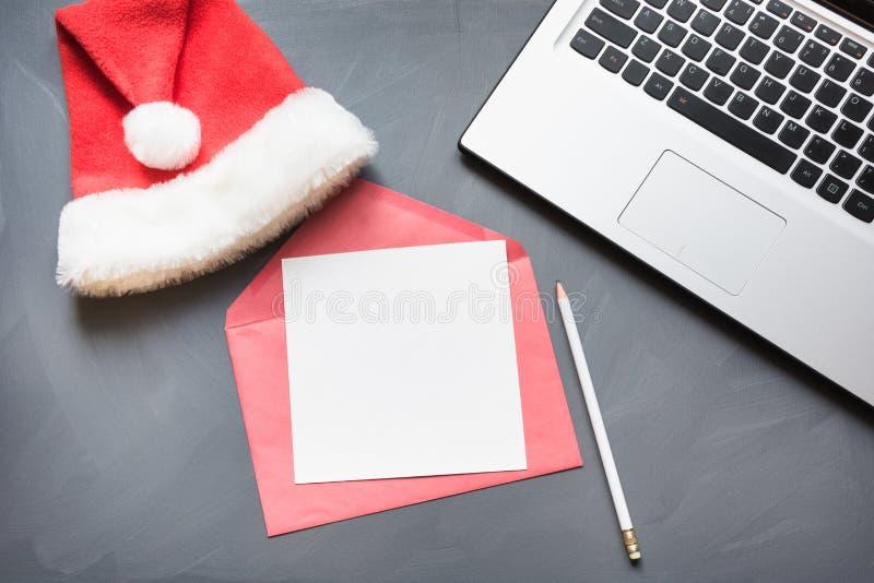 Biurowy miejsce pracy z laptopem, Santa ` s nakrętka, akcesoria na szarym tle Odgórny widok, kopii przestrzeń zdjęcia royalty free
