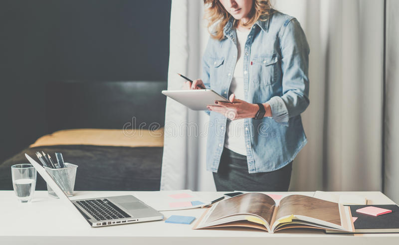 Biurowy projekta studio, młody bizneswoman w drelichowym koszulowym trwanie pobliskim desktop i leafing przez katalogu, fotografia stock