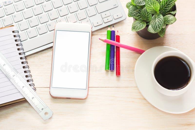 Biurowy workspace z klawiaturową notepad kawą filiżanka i smartphone na drewno stole obrazy royalty free