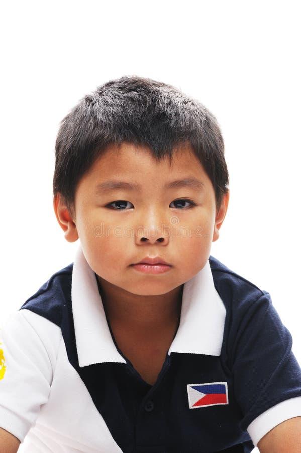 Biy asiatique semble grincheux images stock