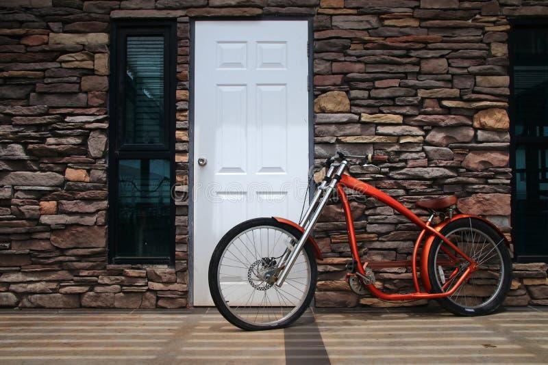 Biycle rouge moderne sur le mur en pierre photographie stock