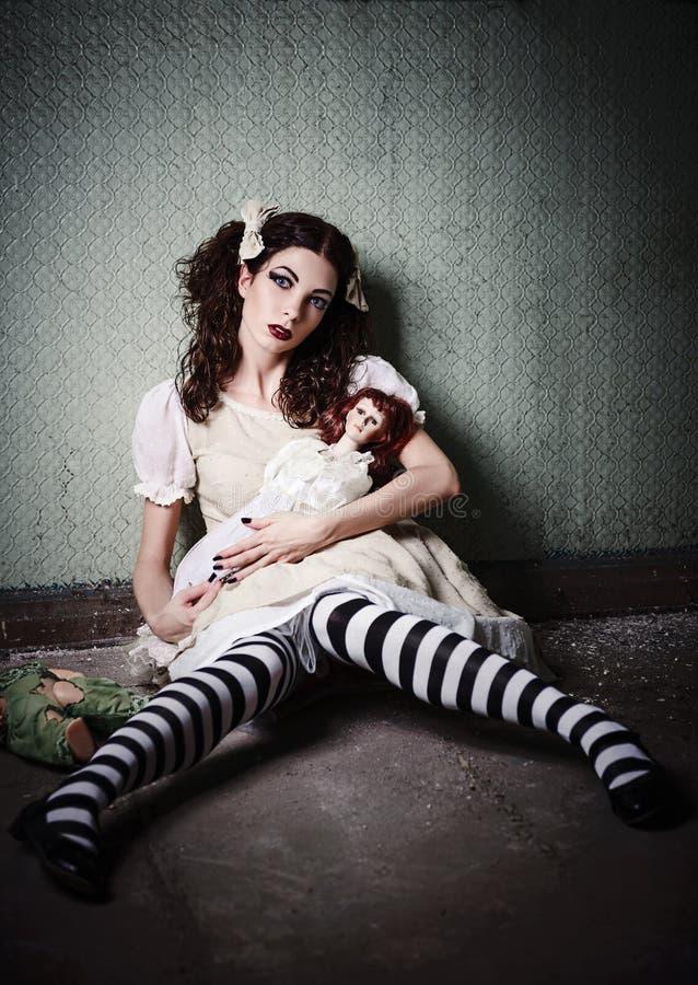 Bizar droevig jong meisje die met poppen in vuile ruimte zitten stock fotografie