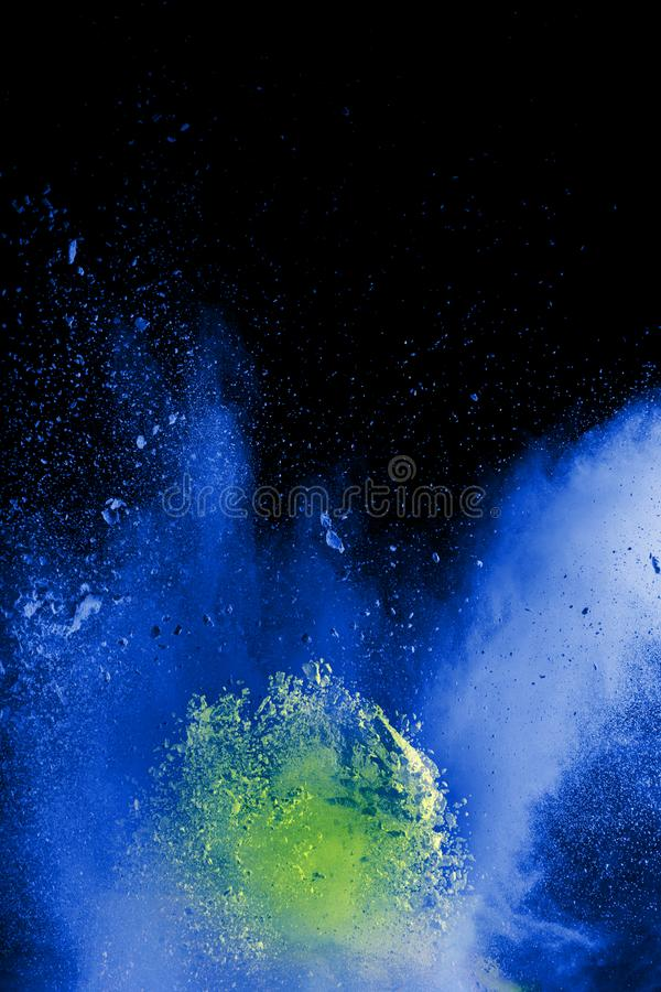 Bizarre forms of blue powder explode cloud on black background. Launched blue dust particles splash on black background royalty free stock photo