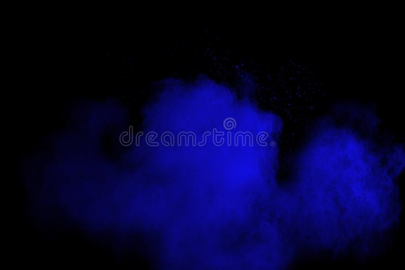 Bizarre forms of blue powder explode cloud on black background. Launched blue dust particles splash on black background royalty free stock photos