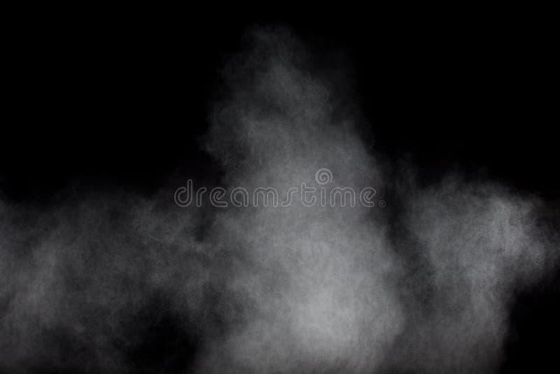 Bizarre forms of white powder explosion cloud against black background.White dust particles splash.  stock photo