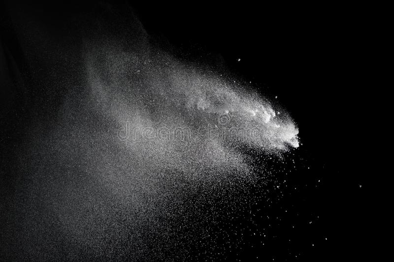 Bizarre forms of of white powder explosion cloud against dark background. Launched white particle splash on black background. Bizarre forms of of white powder stock image