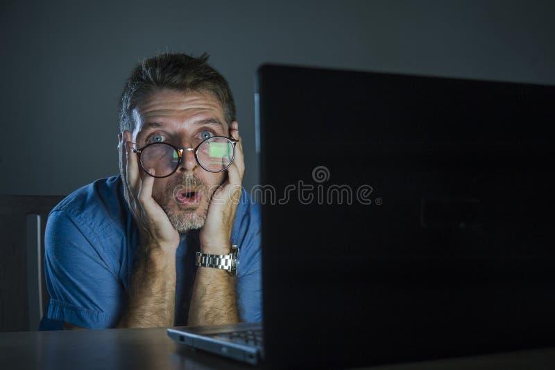 Bizarre geschokt en verrast geek bemannen in nerdglazen die aan laptop computer werken laat - nacht in dark kijkend grappig in sc royalty-vrije stock foto