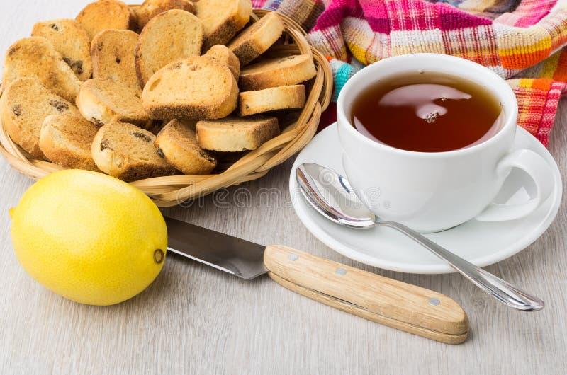 Bizcochos tostados con la pasa en la cesta de mimbre, té, limón, cuchillo fotos de archivo libres de regalías