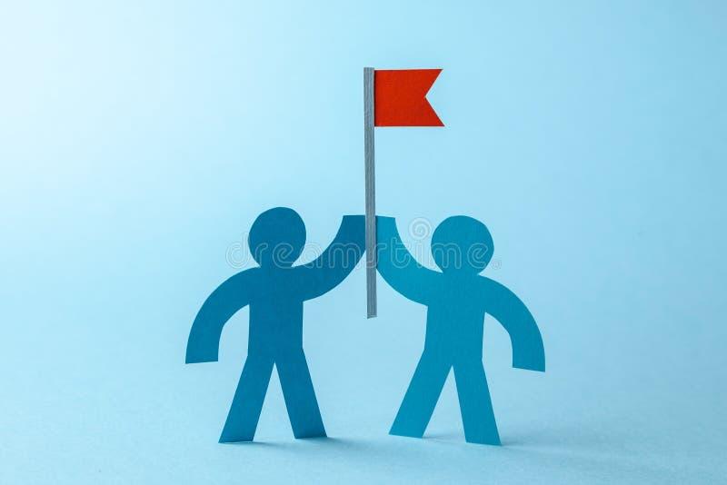 Biznes czerwona flaga z celem i drużyna Drużyna aport dokonywać cel zdjęcia stock